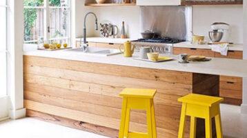 Cuina de fusta combinada amb tamburets grocs