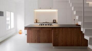Cuina moderna blanca combinada amb fusta i encimera negra