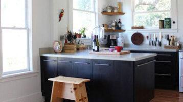 Cuina moderna de fusta negra y parets blanques
